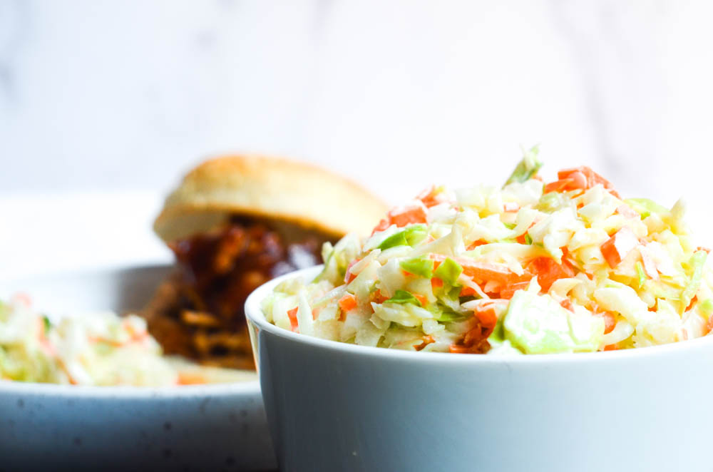 side shot of white bowl of coleslaw with BBQ sandwich in background