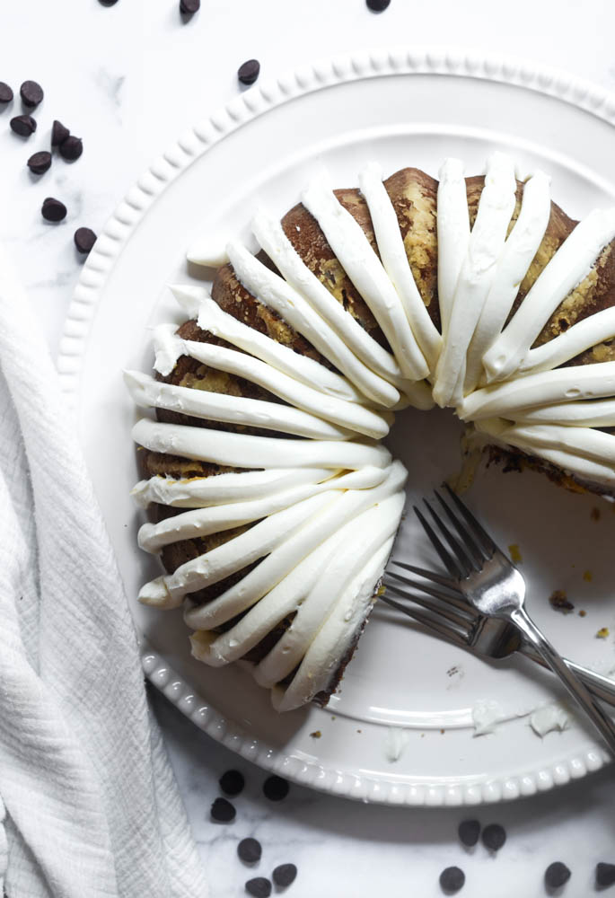 aerial shot of bundt cake on white platter after it's frosted with a few pieces missing