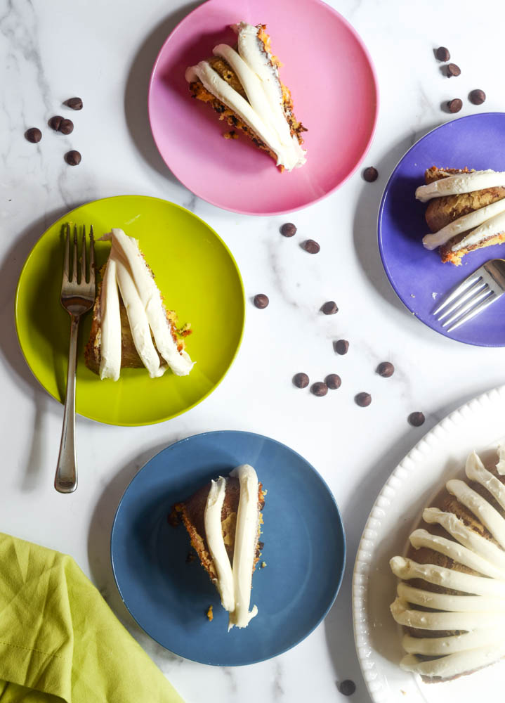 aerial picture of slices of cake on brightly colored plates with forks and chocolate chips scattered