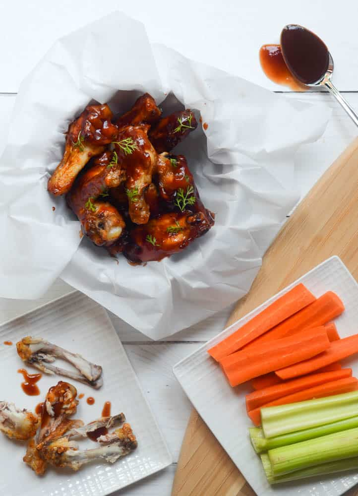 aerial view of bowl o chicken wings in parchment paper nest to square plate with celery and carrots and another plate of chicken wing bones.