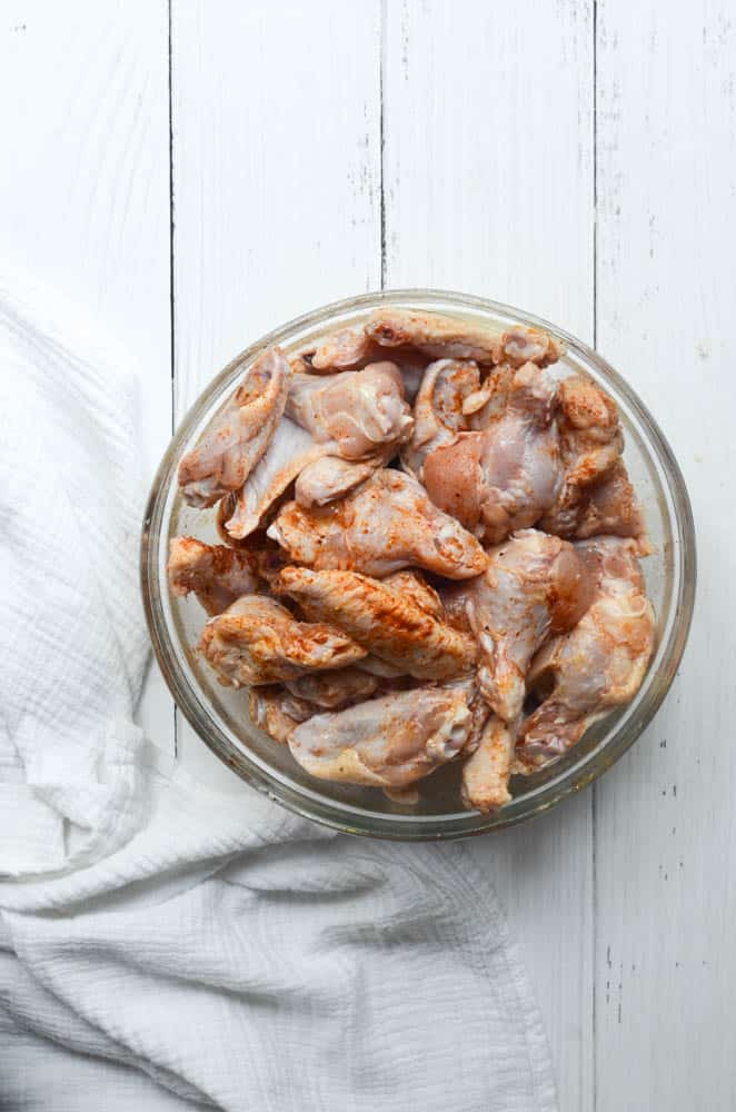 bowl o raw chicken wings coated in seasonings.