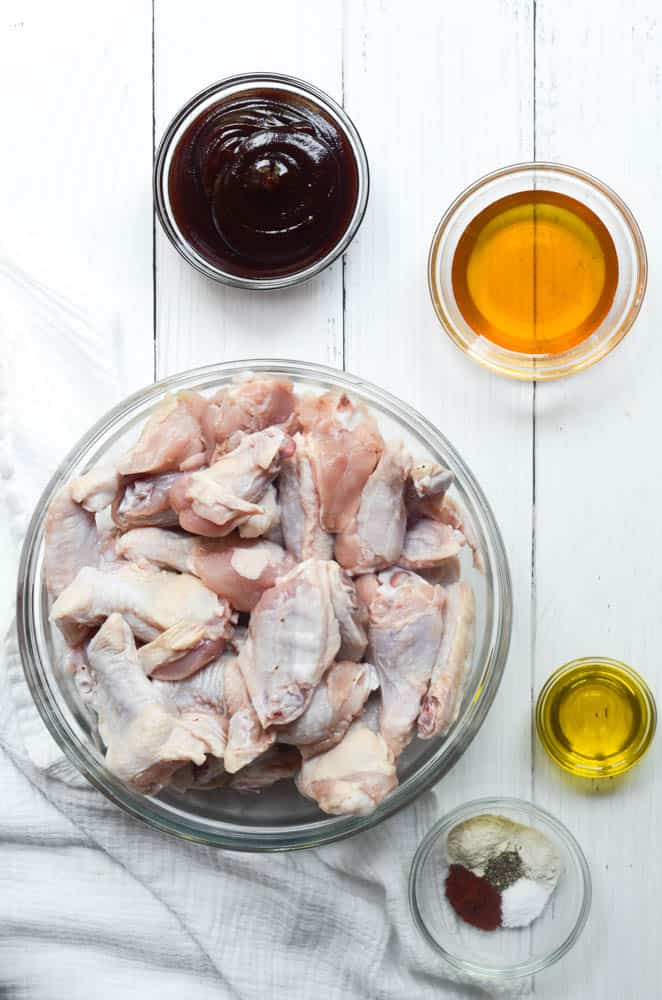 raw chicken wings in bowl with small bowl of spices, olive oil, honey, and BBQ sauce.