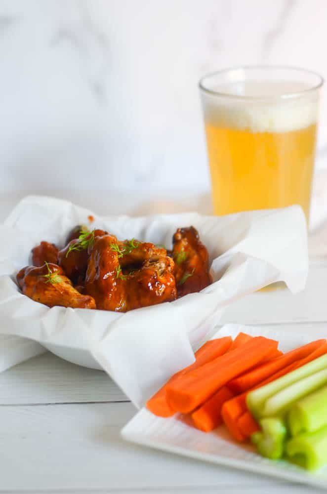 white bowl of chicken wings next to plate of celery and carrots and tall glass of beer.
