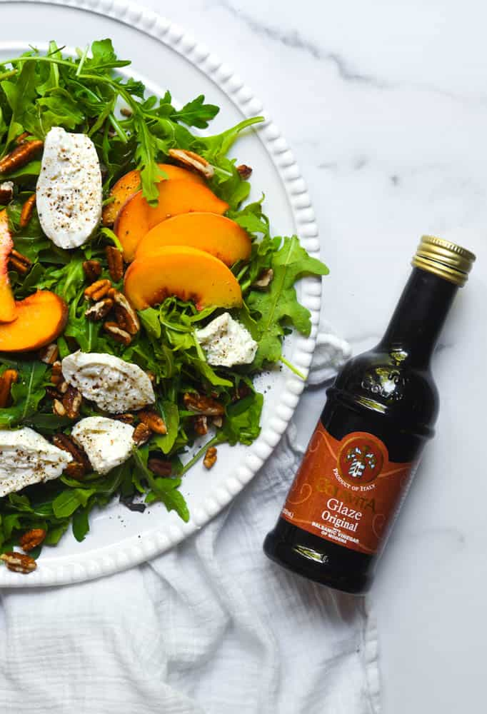 peach salad with burrata, arugula and pecans on white plate next to a bottle of balsamic glaze