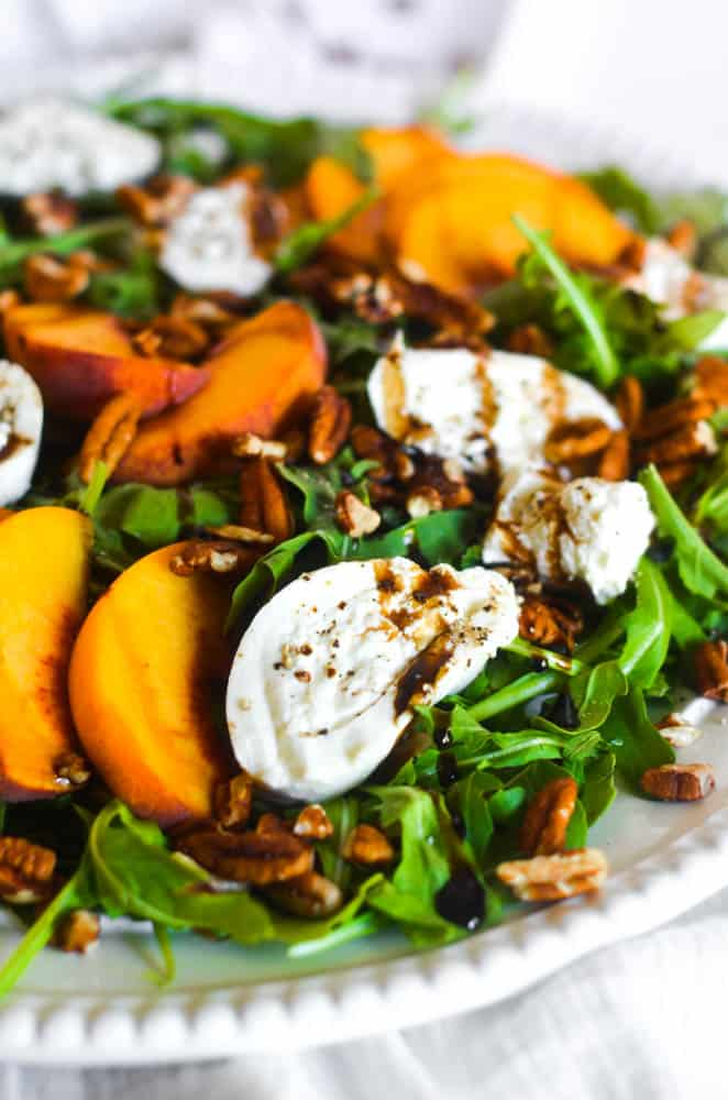 up close picture of burrata on peach salad drizzled with balsamic glaze
