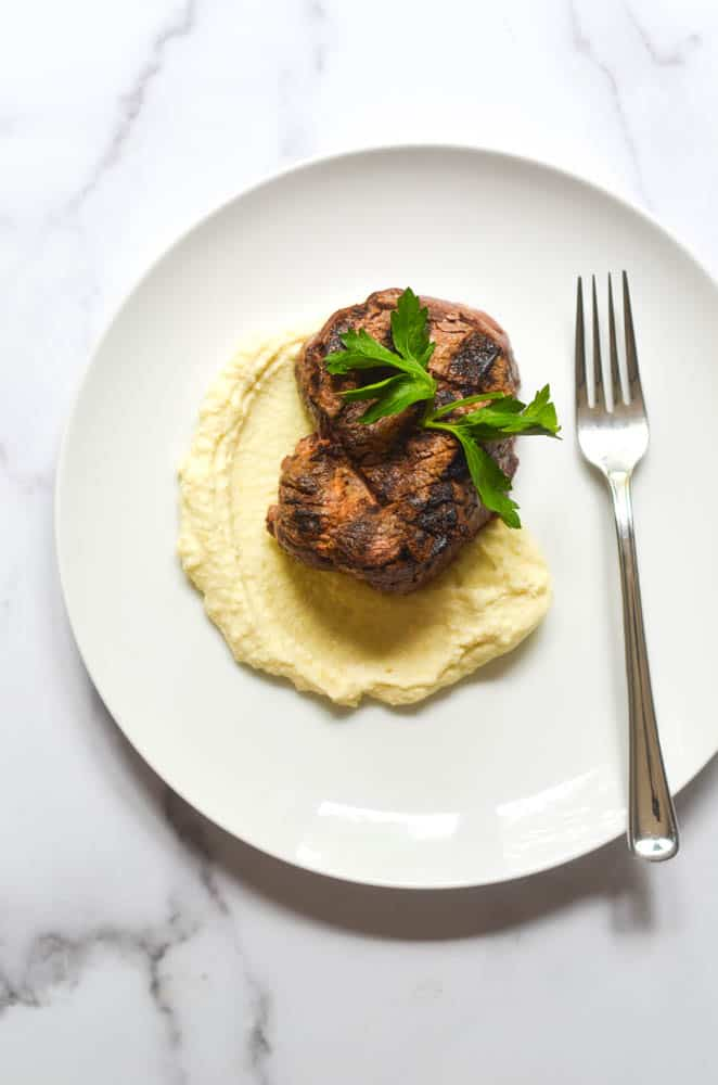 flatlay picture of fillet on bed of mashed potatoes all on white plate and white marble background