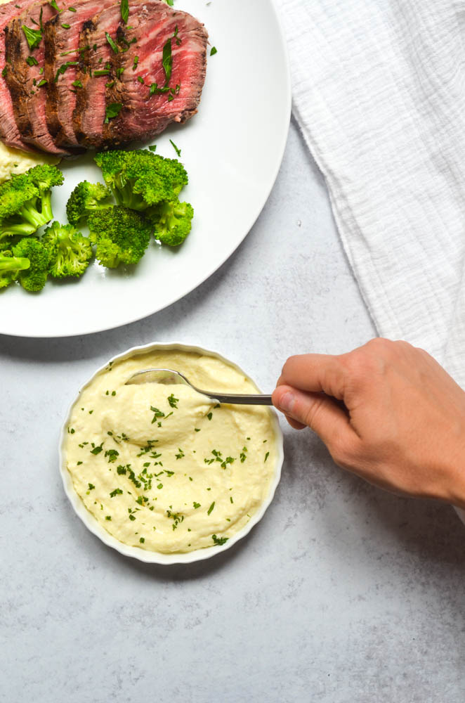 aerial shot of hand scooping pomme puree with a spoon with plate of steak and broccoli next to bowl