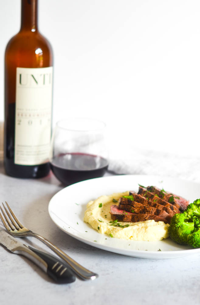 side view of plate of pomme puree, cut steak, and broccoli with bottle and glass of wine in background.