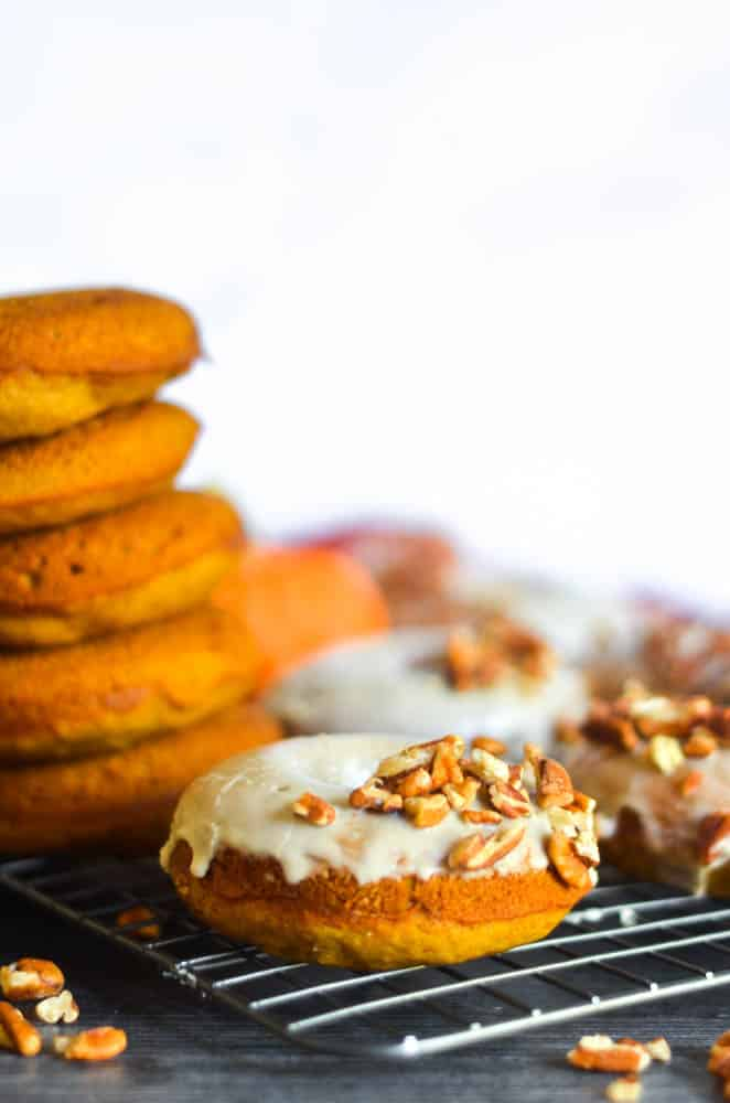 close up of one pumpkin donut glazed and topped with pecan pieces.