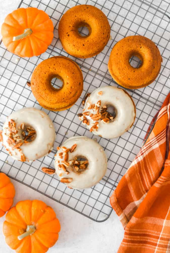 aerial photo of 3 glazed pumpkin donuts and 3 baked donuts on cooling rack.