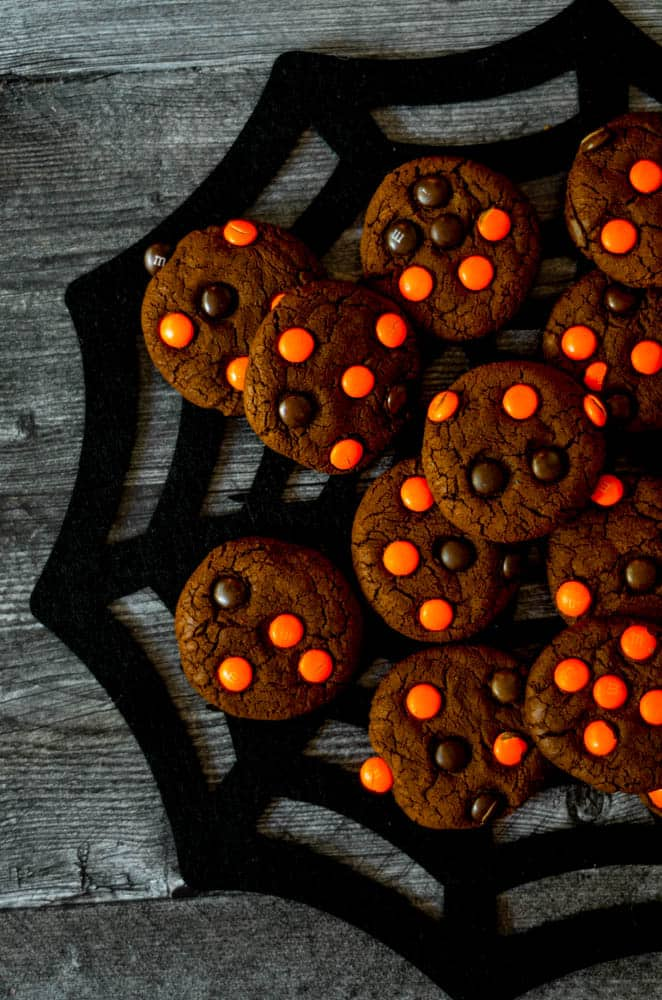 chocolate cookies stacked on top of black spiderweb placemat.