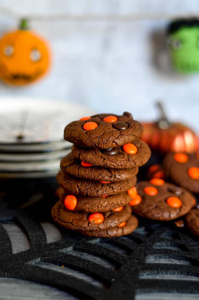 stack of 7 chocolate cookies on black spider web placemat with plates in the background and halloween banner hanging down.