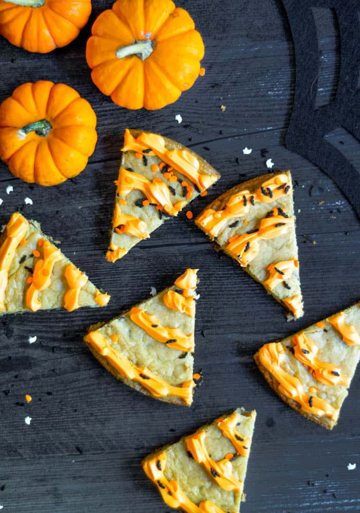 slices of cookie cake on black backdrop with sprinkles and three pumpkins scattered.