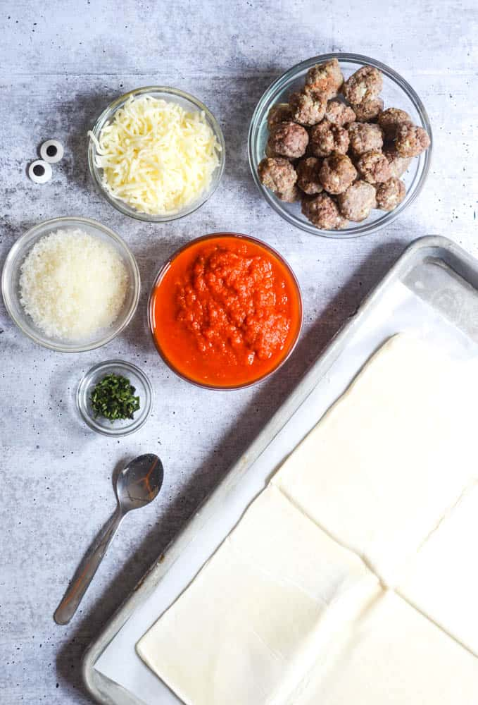 flat lay picture of ingredients needed: puff pastry, basil, marinara sauce, parmesan, mozzarella cheese, meatballs, and candy eyes.