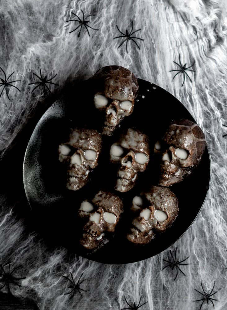 aerial photo of 6 skull chocolate cakes on black plate on top of spider web.