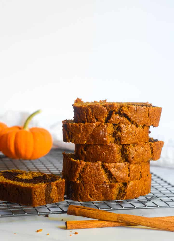 stacked slices of pumpkin chocolate swirl bread on wire rack with pumpkin in background and cinnamon sticks in foreground.