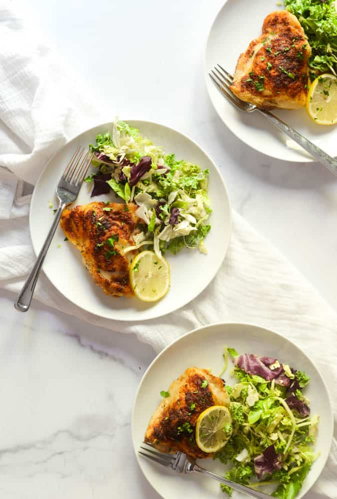aerial flat flay on three white plates with roasted chicken thigh, side salad, and slice of lemon against marble backdrop.