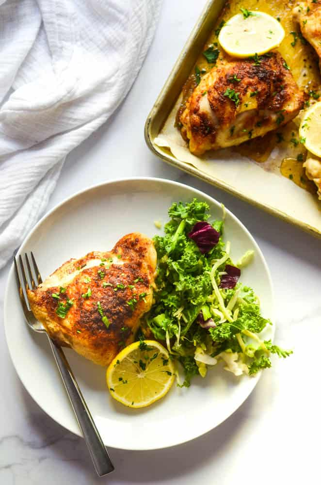 flat lay of one white plate with chicken thigh, side salad, and lemon slice next to sheet pan with other chicken thighs on it.