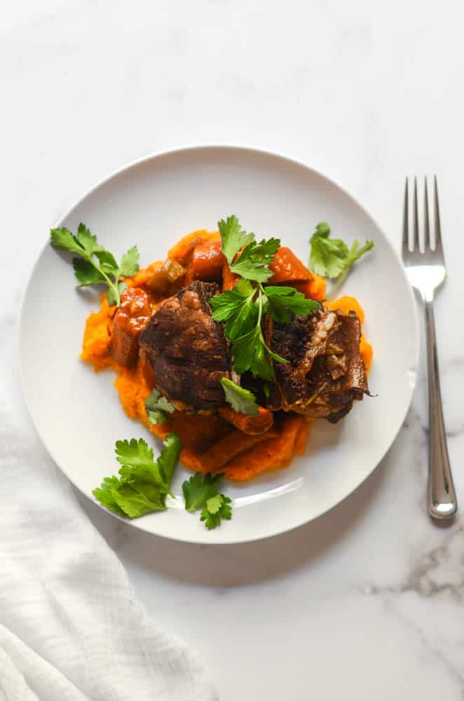 white plate with short ribs on it over bed of mashed butternut squash.