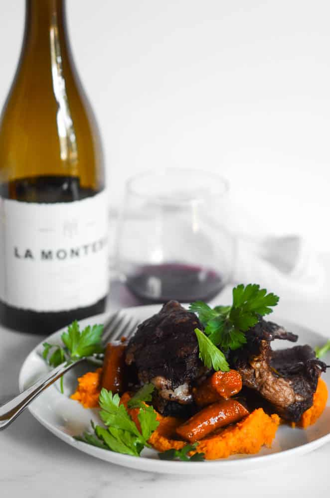 side view of white plate with short ribs and butternut squash and wine bottle and glass in the background.