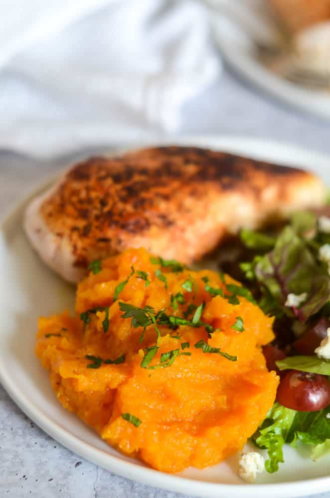 up close picture of butternut squash mash topped with parsley. salad and chicken in the background.