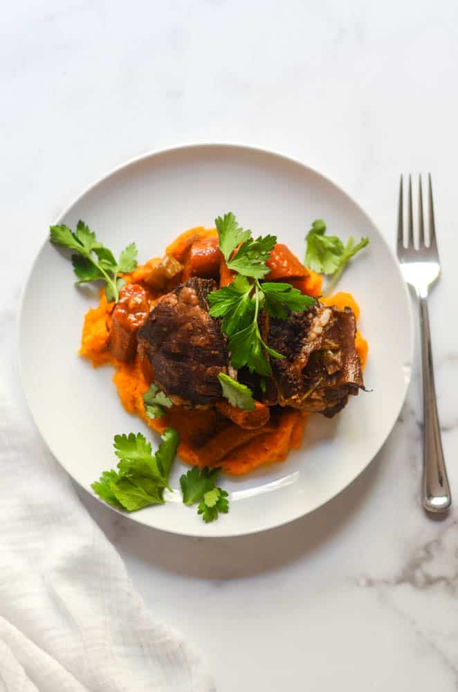 aerial picture of whit eplate with short ribs over a bed of butternut squash mash.