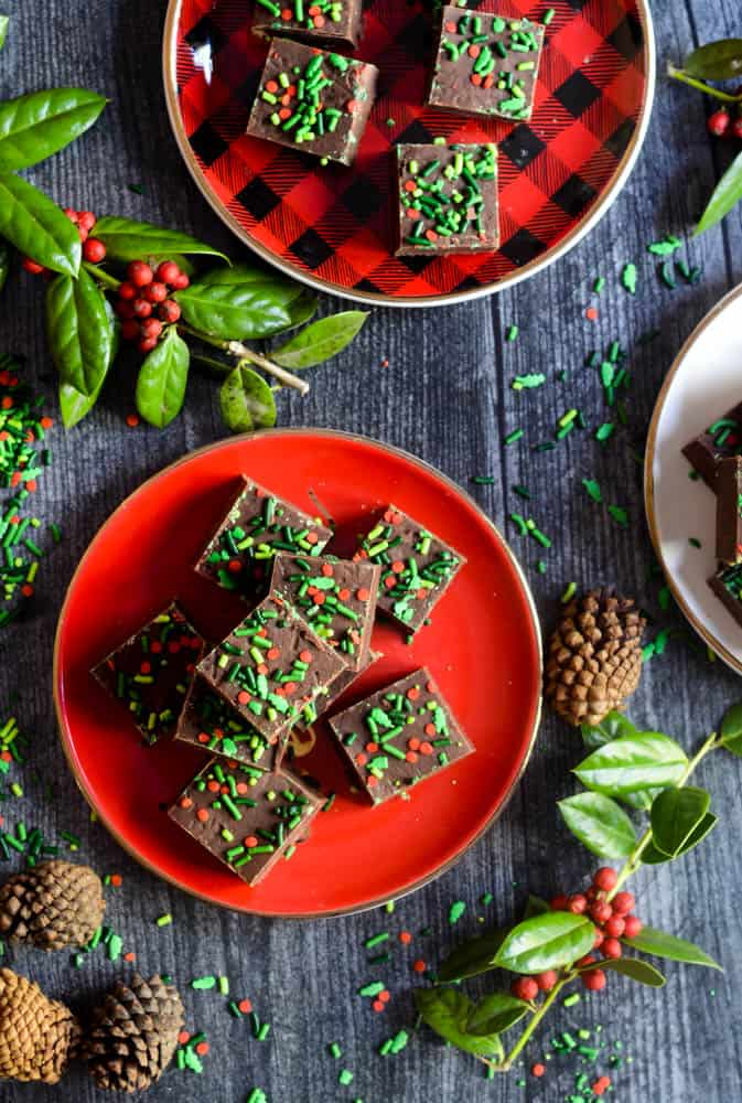 aerial photo of 2 plates with small squares of chocolate fudge stacked on them with holly and pine cones strewn about.