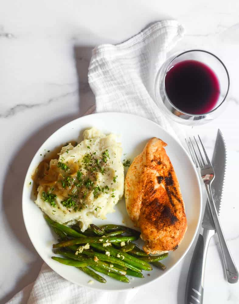 flat lay picture of white plate with dinner on it: chicken breast, mashed potatoes and gravy, and green beans with a glass of red wine.