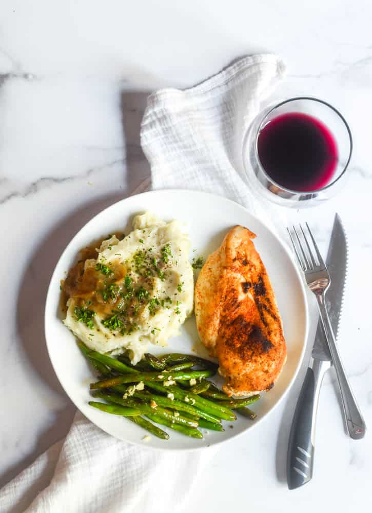 aerial view of whit eplate with green beans, mashed potatoes and gravy, and chicken breast with a glass of red wine.