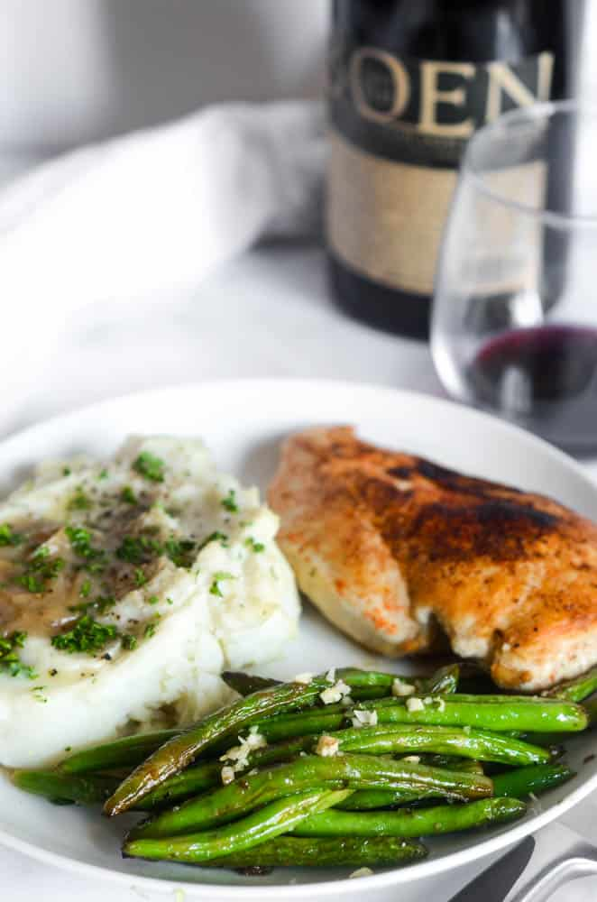 close up picture of white plate with green beans and garlic on top. Mashed potatoes and chicken are in the background.
