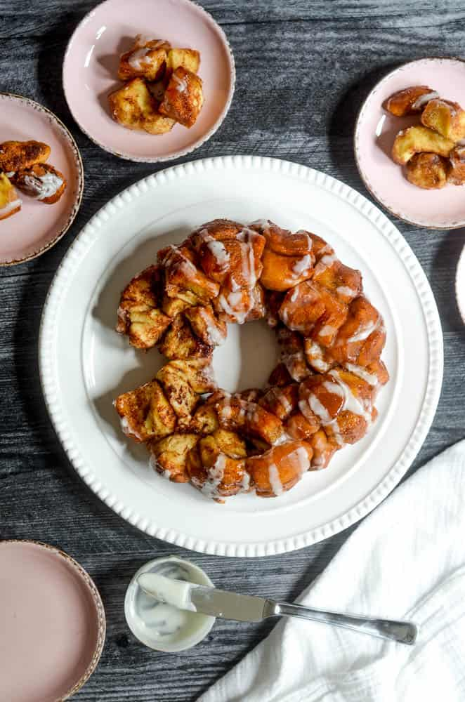flat lay of white platter holding monkey bread on black background surrounded by light pink plates with pieces of bread on them.