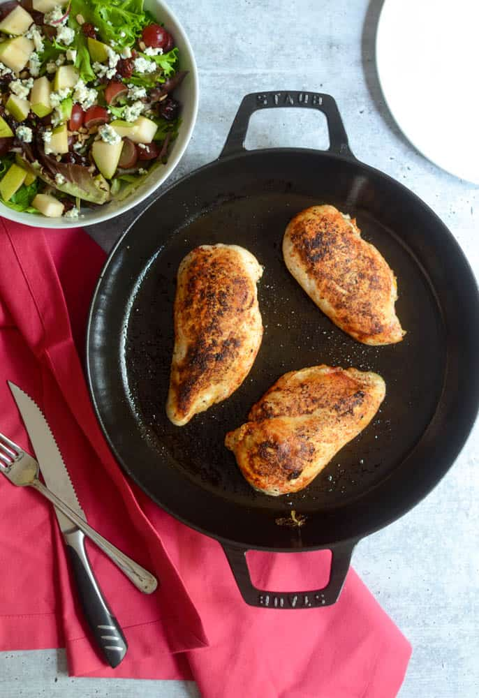 flat lay of 3 seared chicken breasts in cast iron skillet under a pink napkin and side salad in corner.
