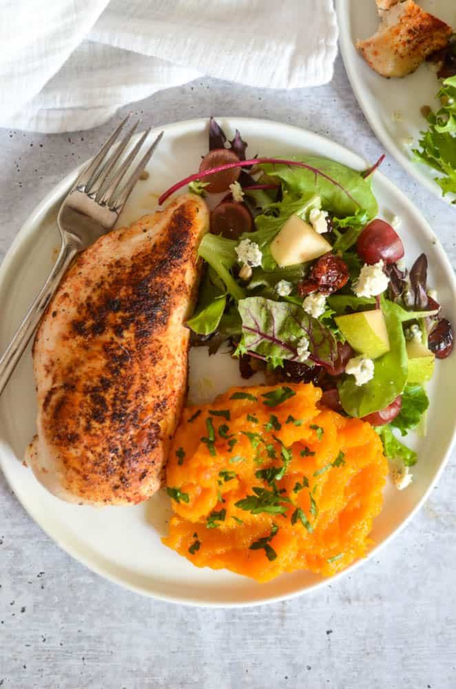 aerial picture of chicken breast, side salad, and butternut squash mash on white plate.