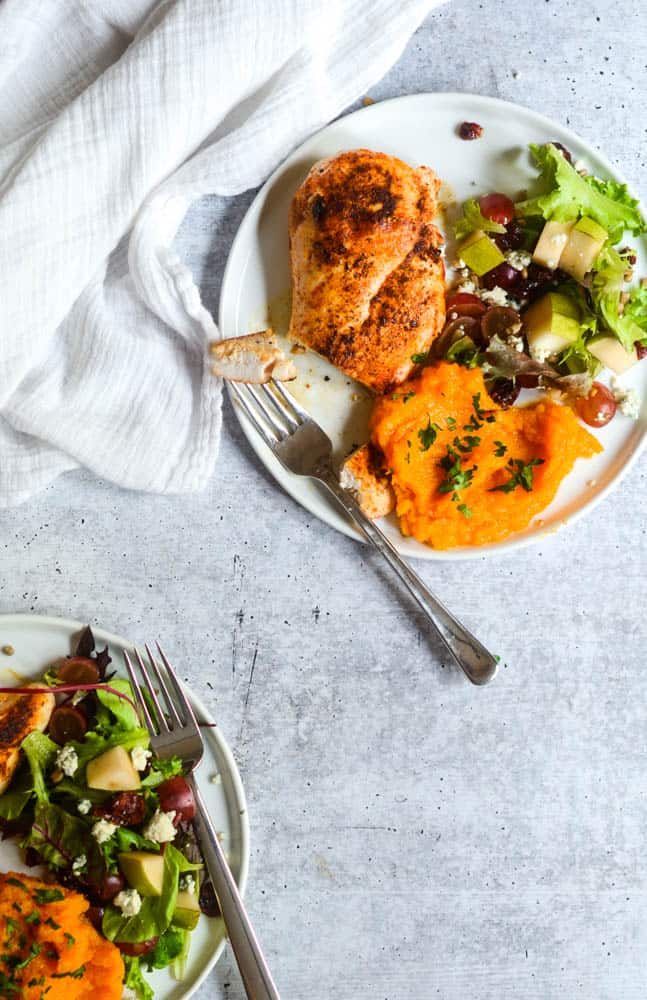 two white plates with chicken breast, butternut squash mash, and salad against concrete background.