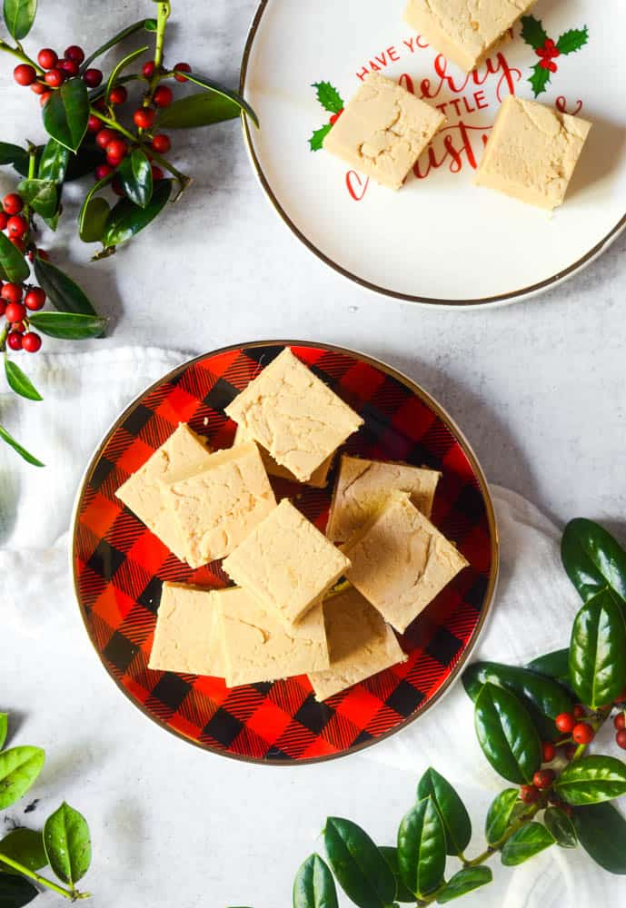 aerial photo of fudge on plaid plate with holly around the frame.