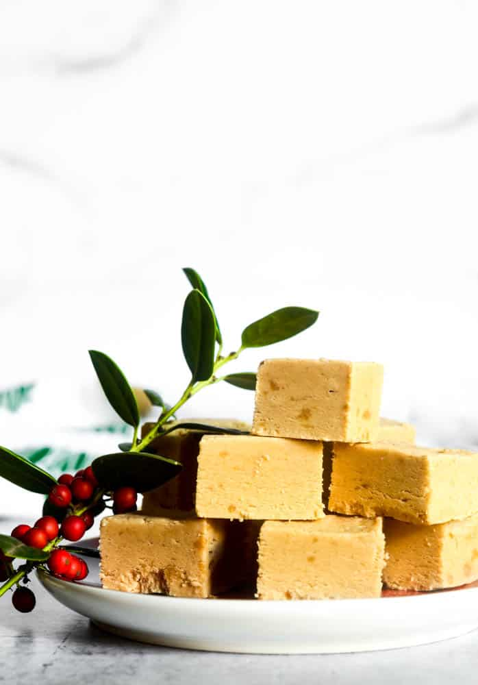 pyramid stack of peanut butter fudge on plate with sprig of holly next to it.