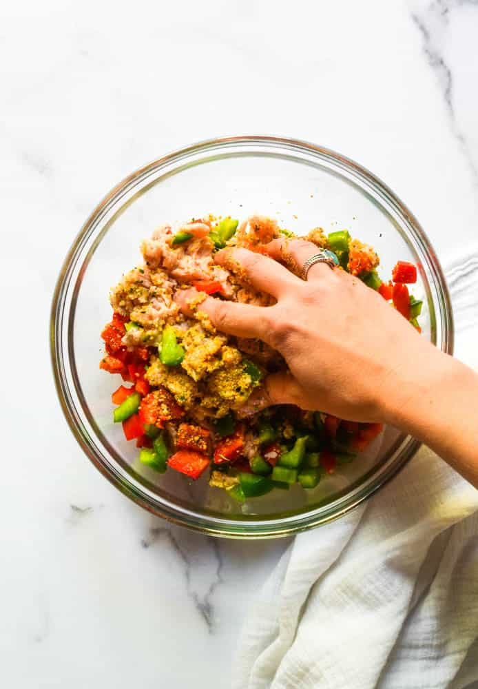 hand mixing the chicken burger ingredients in a glass bowl.
