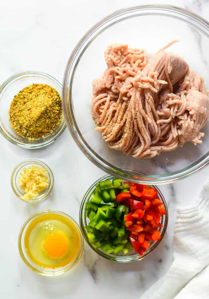 ingredients needed for baked chicken burgers all in separate glass bowls: ground chicken, breadcrumbs, garlic, egg, and bell peppers.