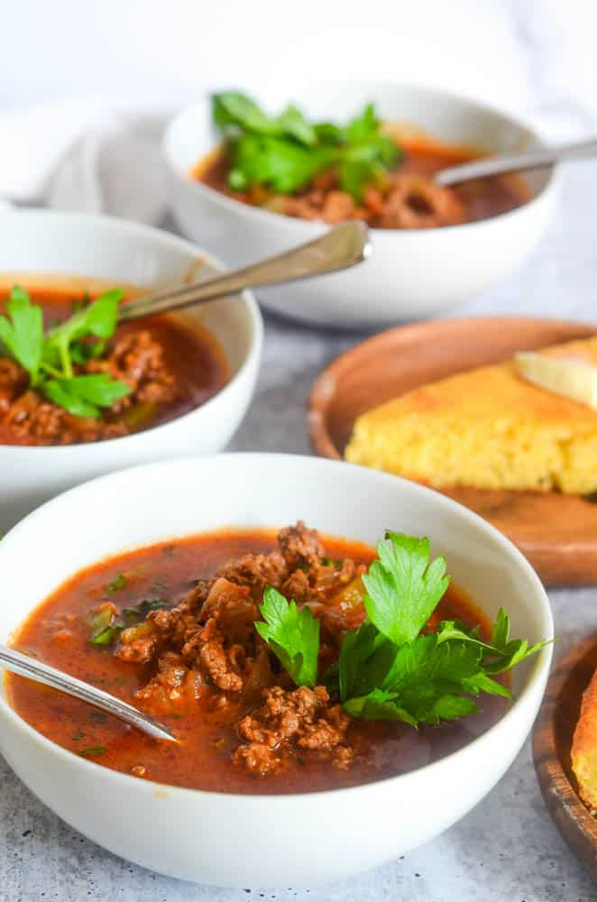 close up picture of one bowl of chili with another bowl of chili and plate of cornbread in the background.