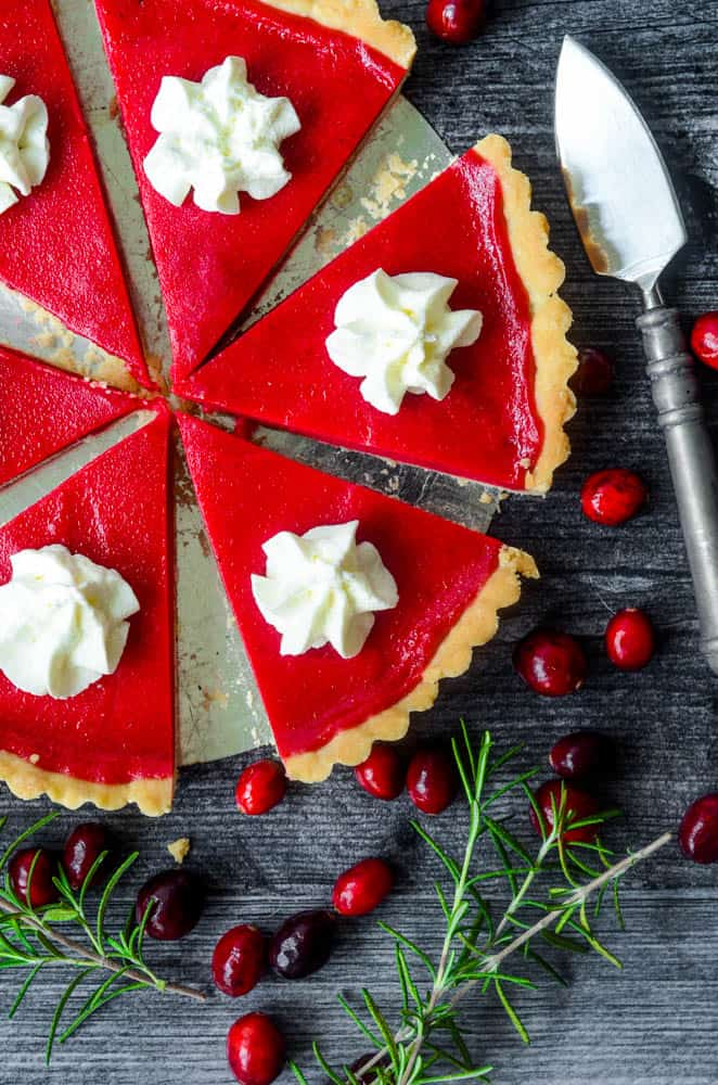 6 slices of cranberry curd tart spread apart with dollop of whipped cream on top all against a black backdrop with cranberries and rosemary scattered around.
