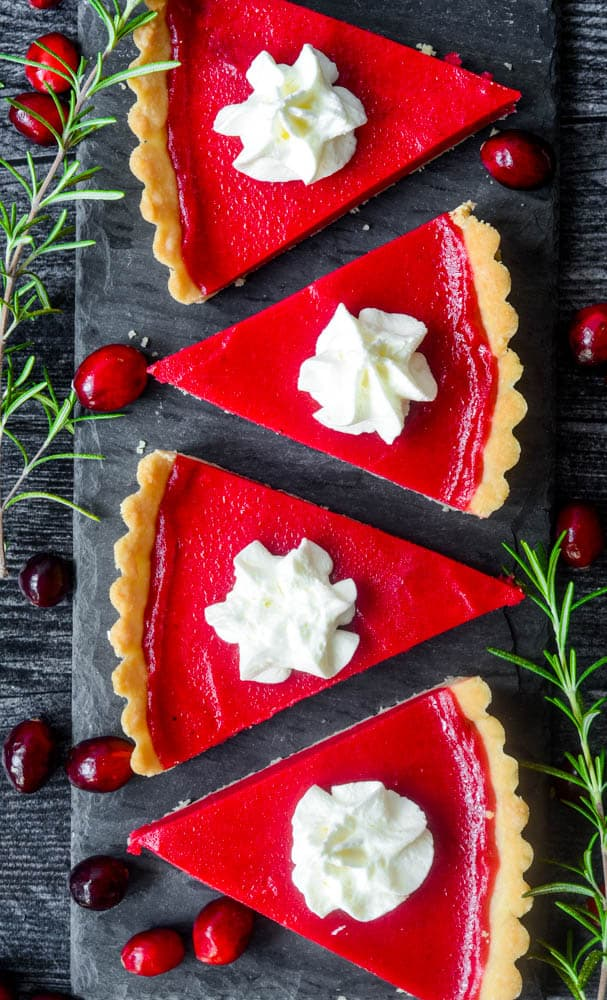 four slices of cranberry tart lined up on black rectangular plate.