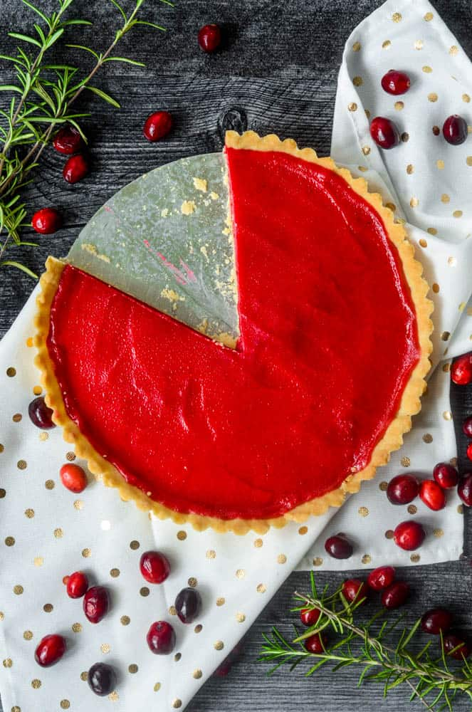 cranberry curd tart with once large slice cut from it.