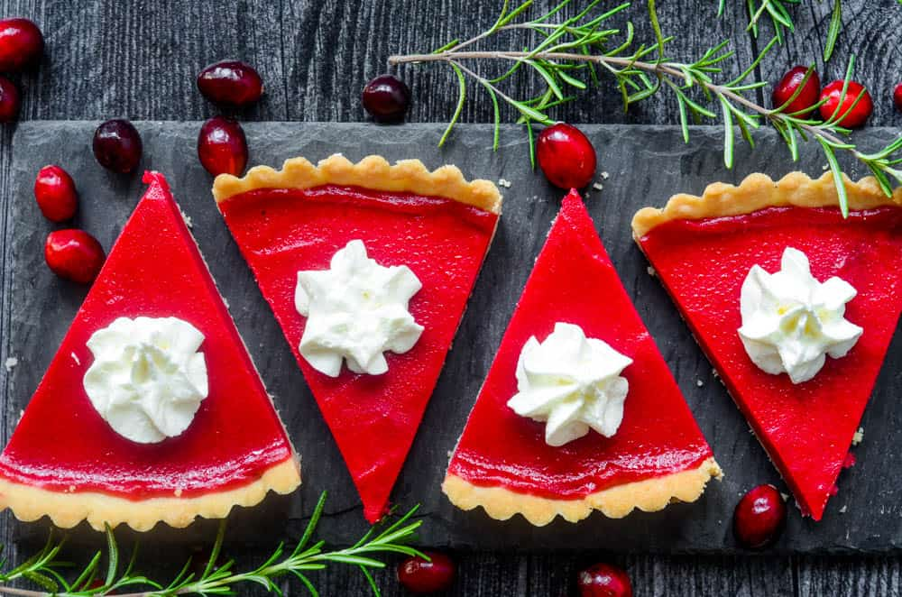 horizontal picture of slices of cranberry curd tart cut on black slate plate with rosemary and cranberries.