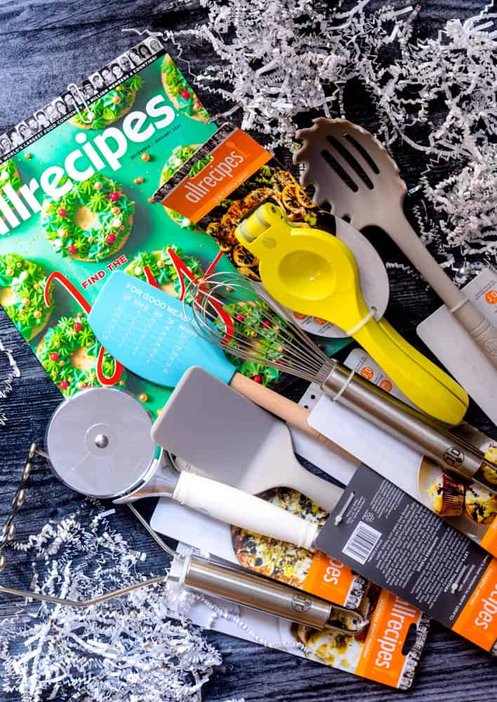 scattered kitchen tools and an all recipes magazine against a black backdrop with confetti.