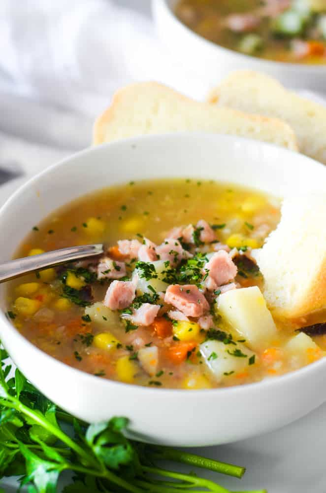 side angle of a bowl of ham soup with ham, corn, potatoes visible and garnished with parsley.