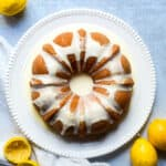 aerial picture of lemon bundt cake on white plate with lemonds around the blue backdrop.