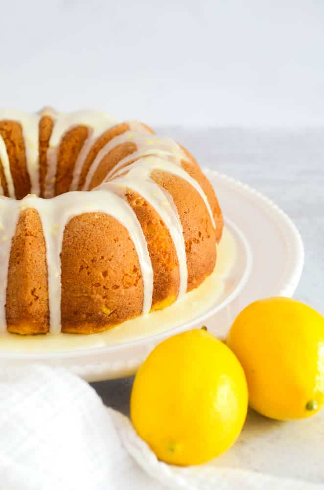 side view of lemon bundt cake on white circular plate with two lemons in the foreground.