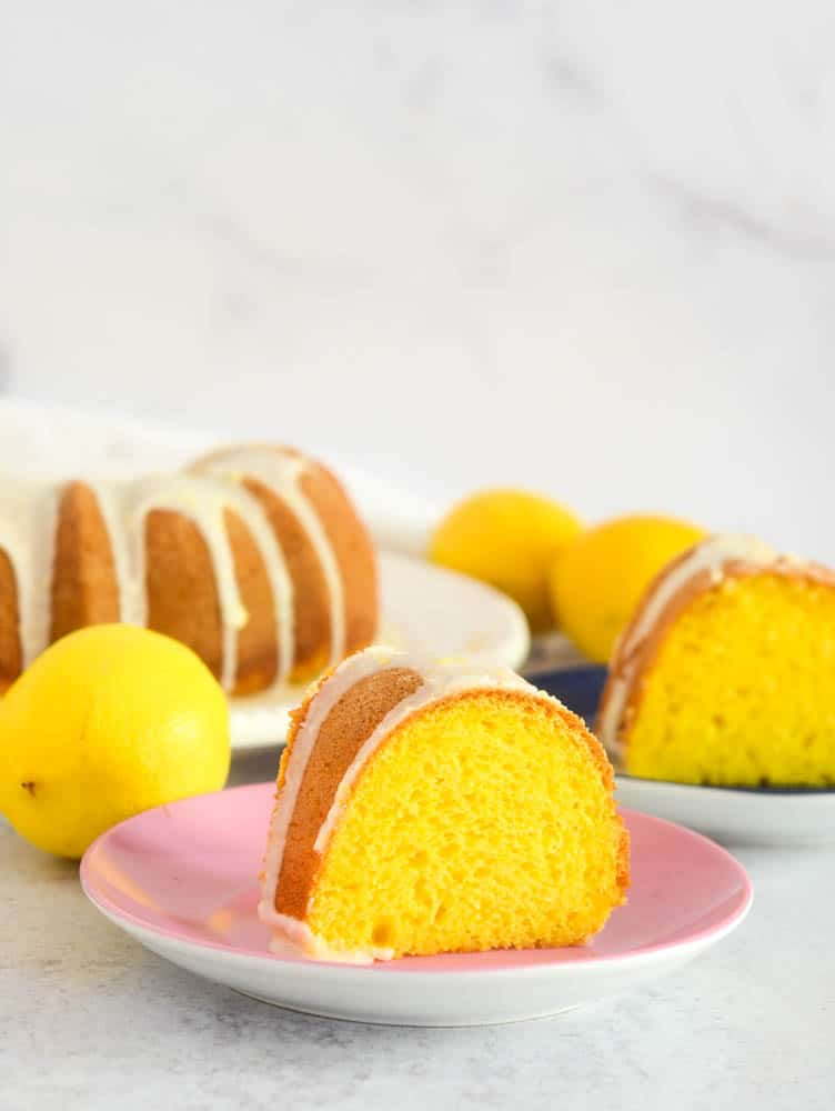 side shot of slice of lemon cake with lemons and another slice of cake in the background.