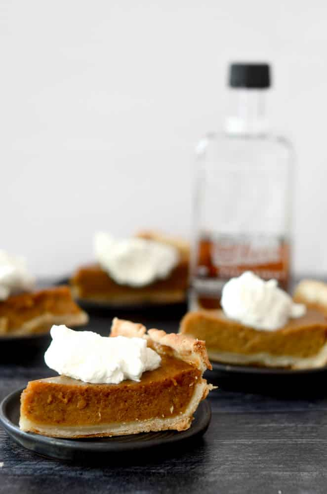 side shot of pumpkin pie slices with bottle of maple syrup blurry in background.
