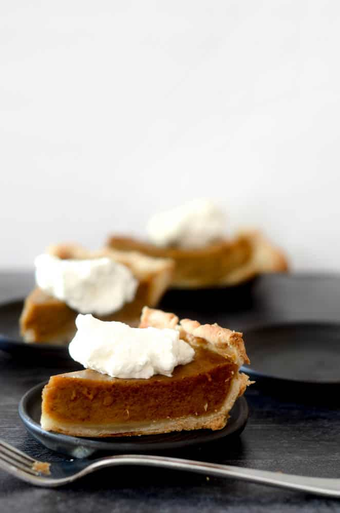side shot of one slice of pumpkin pie with whipped cream on small black plate. fork is resting in front of plate with other pumpkin pies blurry in background.